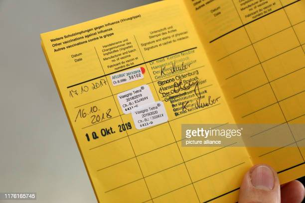 10 October 2019 MecklenburgWestern Pomerania Rostock In the health department one employee shows a vaccination card with the entry for the influenza...