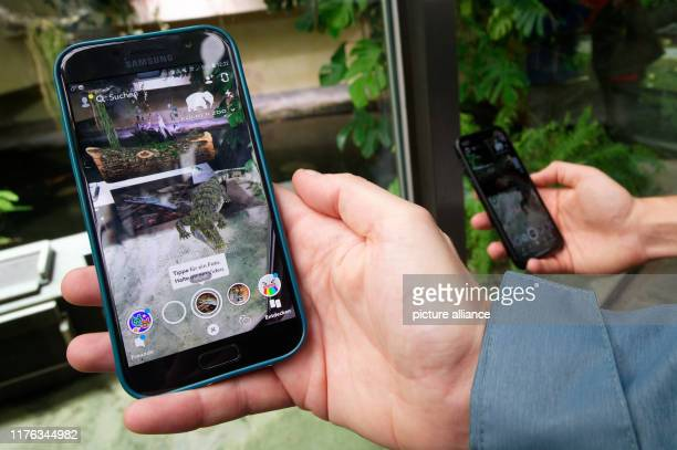 October 2019, North Rhine-Westphalia, Cologne: At a press conference at Cologne Zoo on the zoo's collaboration with Snapchat, a participant holds a...