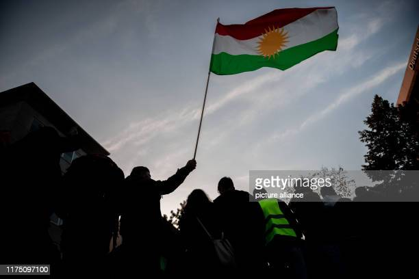 October 2019, North Rhine-Westphalia, Duisburg: A man holds a Kurdish flag in the air as the Kurds demonstrate against the Turkish invasion of Syria....