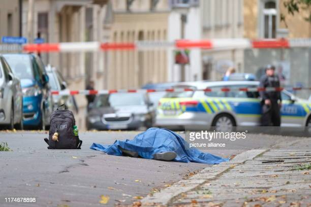 There's a covered body in a street According to initial findings two people were killed in gunfire Photo Sebastian Willnow/dpaZentralbild/dpa