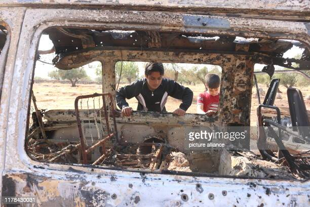 October 2019, Syria, Barisha: Syrian children inspect a burnt vehicle at the site near the northwestern Syrian village of Barisha in the province of...