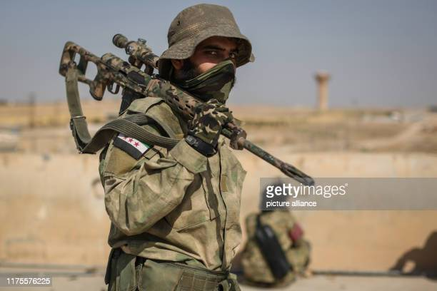 October 2019, Syria, Tell Abiad: A sniper from the Turkish-backed Syrian National Army satnds on a rooftop at Suluk town in the countryside of Tell...