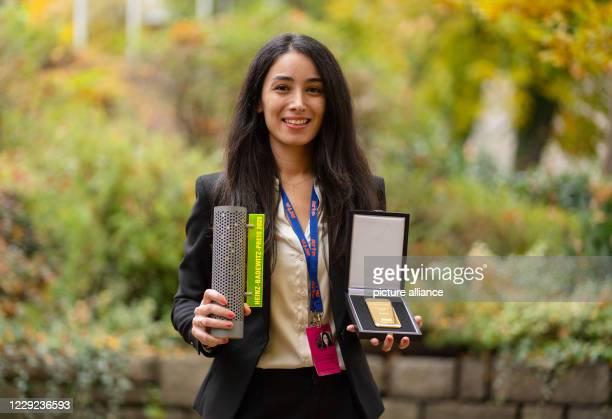 """October 2020, Bavaria, Hof: The director Sevgi Hirschhäuser holds a 1kg gold bar and the Hofer gold price in her hands. Sevgi's debut film """"Tobrak""""..."""
