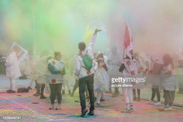 October 2020, Hamburg: Participants in a nationwide warning strike by trainees in the public service demonstrate with bright Holi colours in front of...
