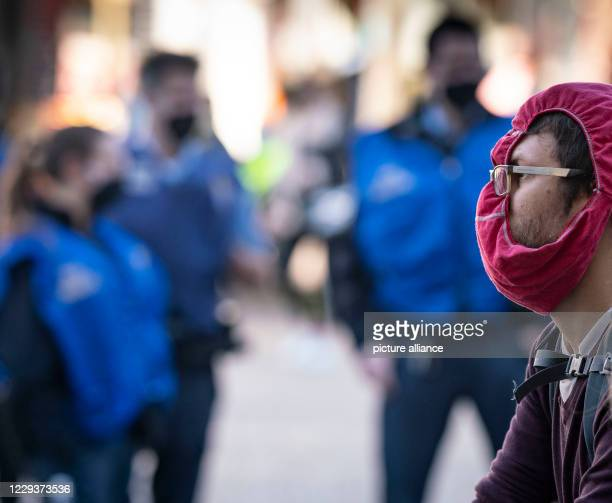 October 2020, Hessen, Darmstadt: A demonstrator wearing panties as mouth and nose protection walks through the city centre to protest against the...