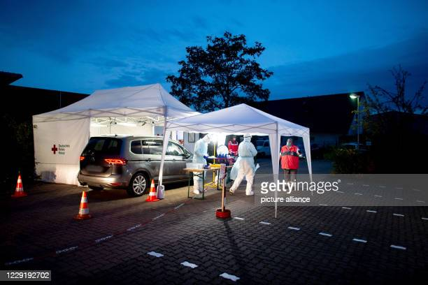 October 2020, Lower Saxony, Ronnenberg: Volunteers from the German Red Cross take a smear test of patients in the Corona Drive-In test centre in the...
