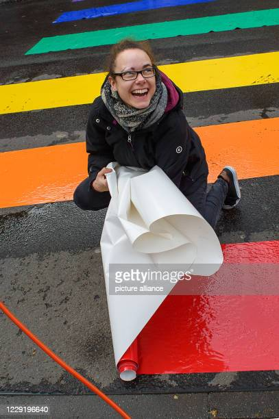 21 October 2020 SaxonyAnhalt Magdeburg Anika laughs and sticks a last red zebra crossing on the asphalt of the road The rainbow zebra crossing action...