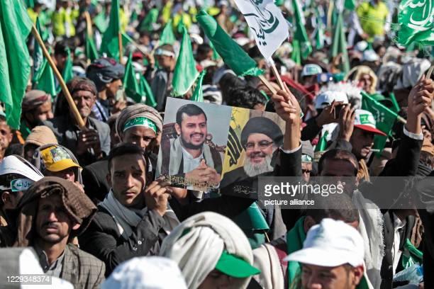 October 2020, Yemen, Sanaa: A man holds a poster of Lebanon's Hezbollah leader Hassan Nasrallah and Shiite Houthi movement's leader Abdul-Malik...