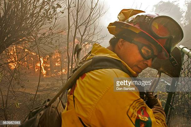 October 22 2007 Escondido CA A California Department of Forestry firefighter uses a shovel to shield his face from the heat of a burning house on...