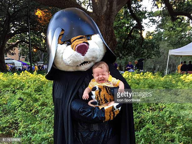 LSU Tigers mascot 'Mike the Tiger' poses with a baby during Ole Miss Rebels at LSU Tigers SEC game at Tiger Stadium in Baton Rouge LA