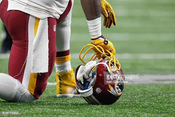 A Washington Redskins player kneels on his helmet during game action between the Washington Redskins and the Detroit Lions during a regular season...