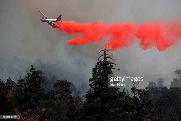 October 25 2007 – – An air–tanker drops fire retardant on the ridges to create a fire containment line near Snow Valley
