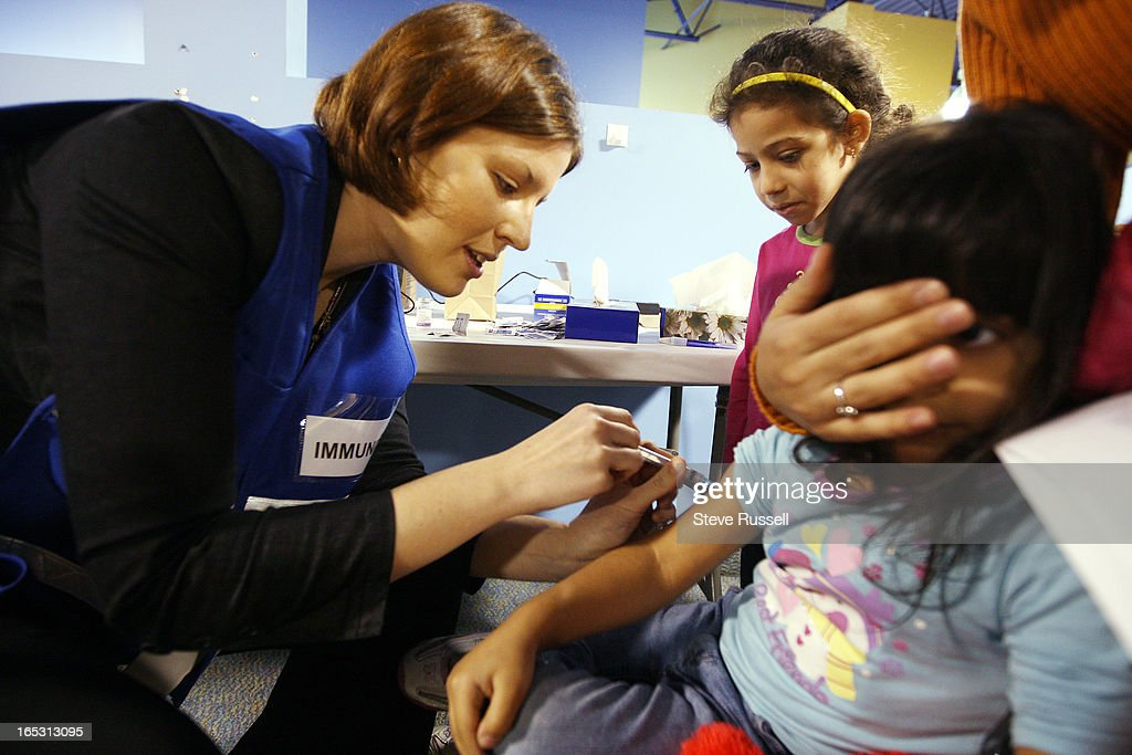 October 26, 2009 Public health nurse Carly McKinnon gives Maya Ahmed her vaccination as her sister R : ニュース写真