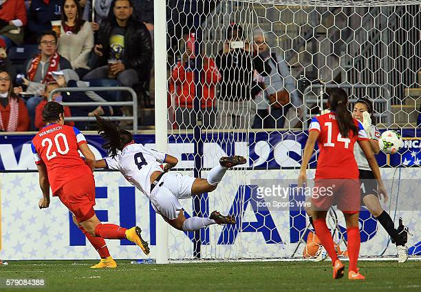 Abby Wambach of the USA sends a header past Daniela Cruz and Dinnia Diaz of Costa Rica for the first goal during the championship match of the...