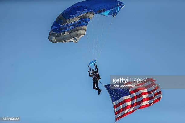 A member of the US Air Force 'Wings of Blue' Parachute Team glides into the stadium before a game between The University of Alabama Crimson Tide and...