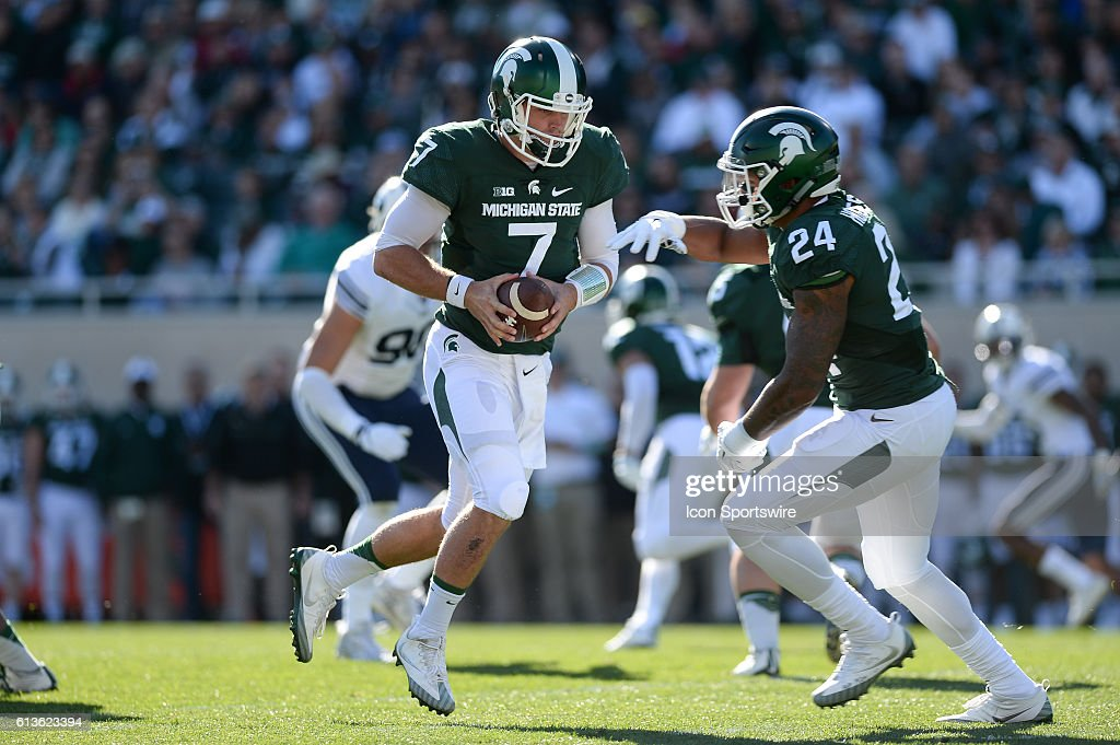 Spartans quarterback Tyler O'Connor (7) hands the ball off to running back Gerald Holmes (24) during a non-conference NCAA football game between Michigan State and BYU at Spartan Stadium, East Lansing, MI.