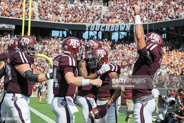 Texas A&M Aggies wide receiver Christian Kirk is swarmed by teammates as Texas A&M Aggies quarterback Trevor Knight signals touchdown during first...
