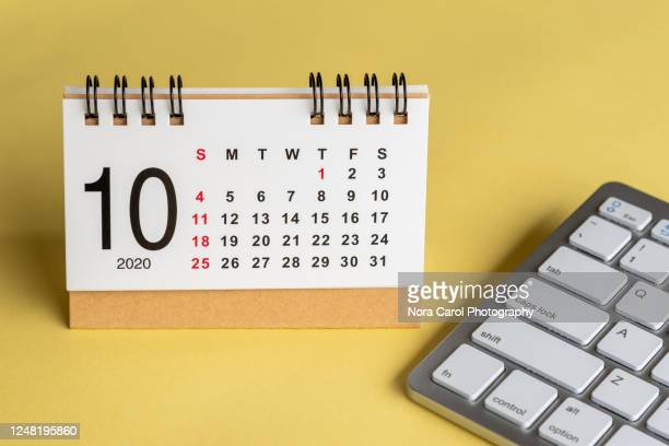 october calendar on yellow background - october stock pictures, royalty-free photos & images