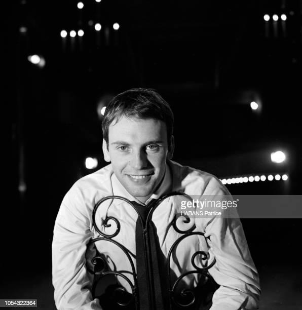 Octobre 1960 Rendezvous avec JeanLouis TRINTIGNANT répétant son texte au théâtre de face souriant sur scène assis à califourchon sur une chaise