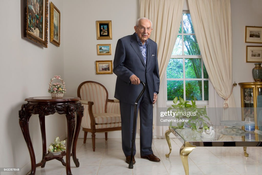 Octogenarian man in suit standing in well appointed living room. : Stock Photo