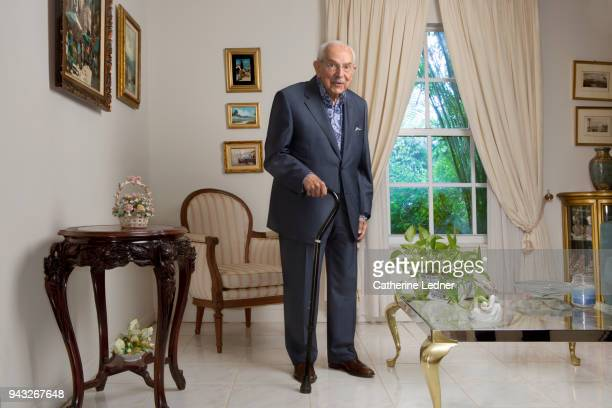 Octogenarian man in suit standing in well appointed living room.