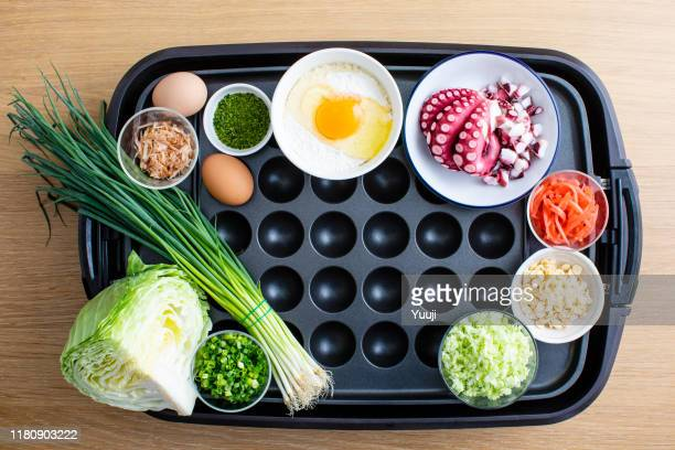 octopus grill recipe. on the iron plate, materials such as octopus, leeks, eggs, flour, cabbage, and bonito are placed. angle shot from above. - tenkasu stock pictures, royalty-free photos & images