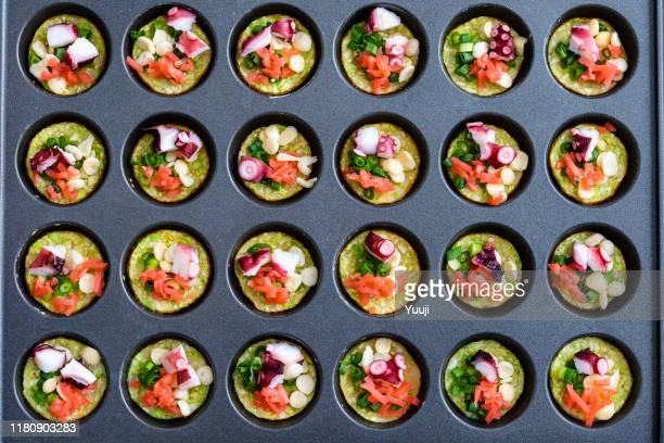 octopus grill recipe. put the cut takoyaki material into the hole in the iron plate.angle shot from above. - takoyaki stock pictures, royalty-free photos & images