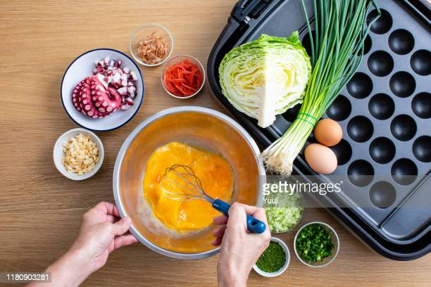 octopus grill recipe. takoyaki machine and raw materials such as octopus, long onion, egg, flour, cabbage, bonito, etc. are placed on a bright wood table. senior woman's hands are stirring raw eggs.angle shot from above. - tenkasu stock pictures, royalty-free photos & images