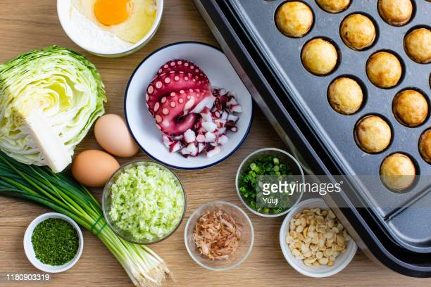 octopus grill recipe. takoyaki machine and raw materials such as octopus, long onion, egg, flour, cabbage, bonito, etc. are placed on a bright wood table. - tenkasu stock pictures, royalty-free photos & images