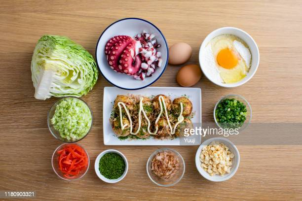octopus grill recipe. takoyaki served on a plate. on the light wood table, the material octopus, flour, eggs, cabbage and long onion are placed.angle shot from above. - tenkasu stock pictures, royalty-free photos & images