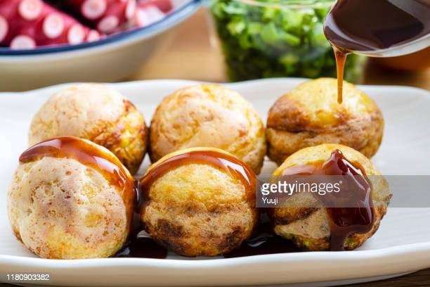 octopus grill recipe. ti'm putting sauce on takoyaki. around. there are octopus, flour, egg, cabbage and long onion. - takoyaki stock pictures, royalty-free photos & images