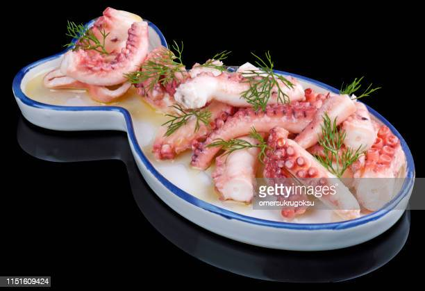 octopus salad in fish-shaped platter on black background - kraken stock photos and pictures