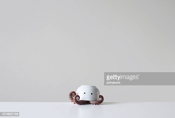Octopus tentacles under an upside down bowl with two eyes