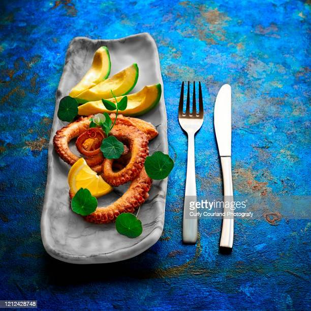 octopus with avocado, nasturtium, lemon and green pea sprouts on the marbled plate - aperitivo plato de comida - fotografias e filmes do acervo