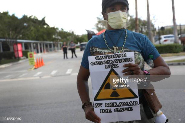 Odalys K Fernandez holds a sign reading Caution Coronavirus risk at Miramar Ice cage as she joins protesters outside of a US Immigration and Customs...