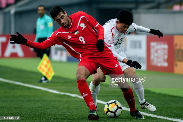Oday Dabbagh of Palestine and Kang II KukChol of North Korea compete for the ball during the AFC U23 Championship Group B match between Palestine and...