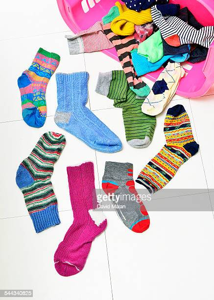 odd socks spilling out of a basket - mismatched clothes stock pictures, royalty-free photos & images
