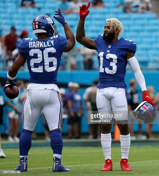 Odell Beckham and teammate Saquon Barkley of the New York Giants greet each other during warm ups against the Carolina Panthers at Bank of America...