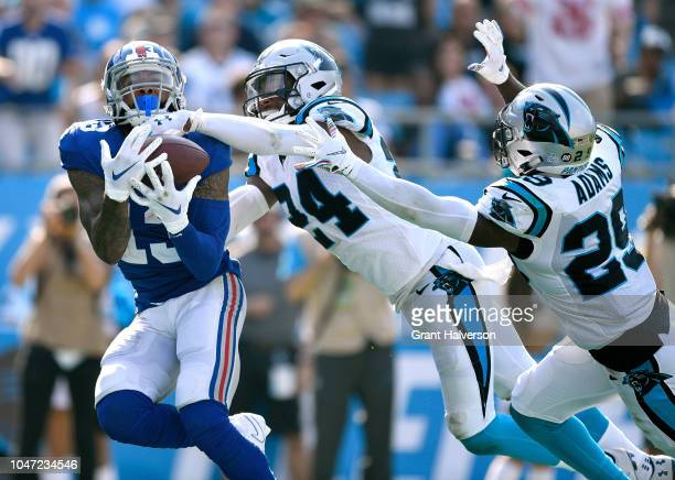 Odell Beckham Jr #13 of the New York Giants makes a touchdown catch against James Bradberry and Mike Adams of the Carolina Panthers during their game...