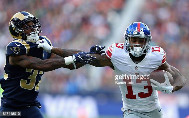 Odell Beckham Jr of the New York Giants hands off Troy Hill of the Los Angels Rams during the NFL International Series match between New York Giants...