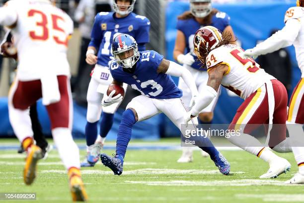 Odell Beckham of the New York Giants jukes against Mason Foster of the Washington Redskins at MetLife Stadium on October 28, 2018 in East Rutherford,...