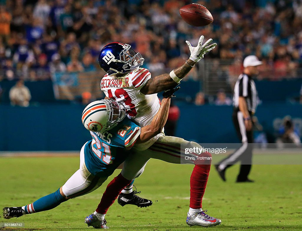 Odell Beckham #13 of the New York Giants reaches for the ball while defended by Brent Grimes #21 of the Miami Dolphins during the second half of the game at Sun Life Stadium on December 14, 2015 in Miami Gardens, Florida.
