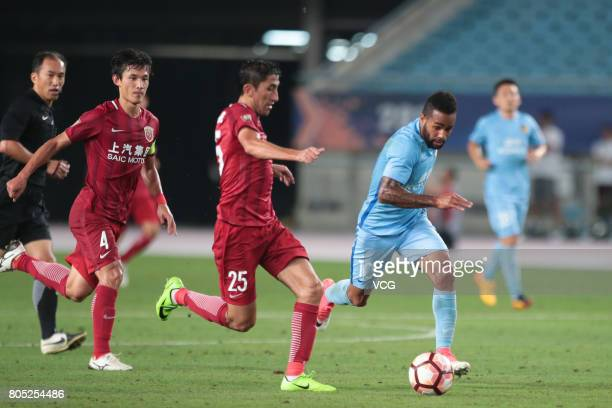 Odil Ahmedov of Shanghai SIPG and Alex Teixeira of Jiangsu Suning compete the ball during 2017 Chinese Super League 15th round match between Jiangsu...