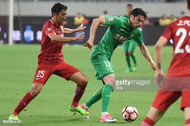 Odil Ahmedov of Shanghai SIPG and Burak Yilmaz of Beijing Guoan compete for the ball during the 11th round match of 2017 Chinese Football Association...