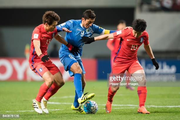 Odil Akhmedov of Uzbekistan fights for the ball with Koo Jacheol and Nam Taehee of Korea Republic during the 2018 FIFA World Cup Russia Asian...