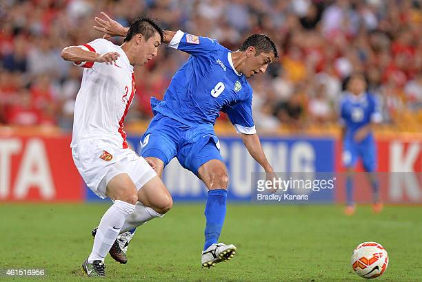 Odil Akhmedov of Uzbekistan is challenged by the defence of Ren Hang of China during the 2015 Asian Cup match between China PR and Uzbekistan at...