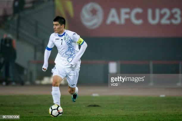 Odiljon Xamrobekov of Uzbekistan drives the ball during the AFC U23 Championship quarterfinal match between Japan and Uzbekistan at Jiangyin Stadium...