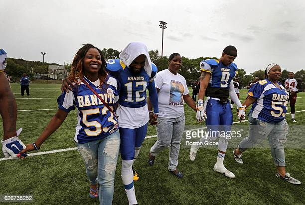 Odin Lloyd' sister's Olivia, at left, and Shaquila Thibou, at far right, both wearing his former Bandits jersey, join with Bandits players and...