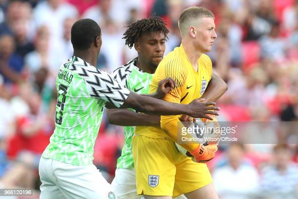 Odion Ighalo of Nigeria and Alex Iwobi of Nigeria wrestle England goalkeeper Jordan Pickford for the ball after Iwobi scores a goal to make it 21...