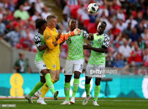 Odion Ighalo of NigeriaVictor Moses of Nigeria and Alex Iwobi of Nigeria attempt to grab the ball off Jordan Pickford of England after Alex Iwobi of...